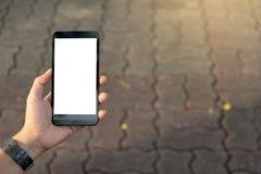 Hand genom att använda den stads- gatan för mobiltelefon arkivbild