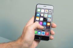 Hand genom att använda en Apple iPhone6 Royaltyfri Bild
