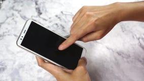 Hand genom att använda smartphonen och knacka lätt på den tomma skärmen för shopping och arbete direktanslutet stock video