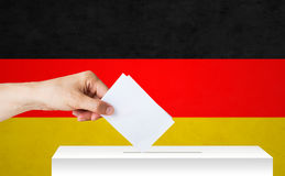 Hand of german with ballot and box on election. Voting, civil rights and people concept - male hand putting his vote into ballot box on election over german flag Royalty Free Stock Images