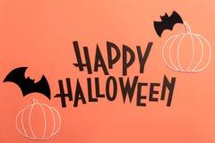 Hand geschreven uitdrukking Gelukkig Halloween met pompoenen en knuppels dichtbij het stock afbeeldingen