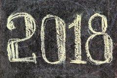 Hand 2018 geschrieben in Kreide auf schwarzes Brett Guten Rutsch ins Neue Jahr-Grüße Lizenzfreie Stockfotos