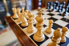 Hand-gesneden die schaakstukken en raad binnen een privé huis worden gezien stock fotografie