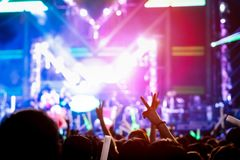 Hand gesture victory finger at concert stage. Lights crowd or audience artist band in the music festival rear view with spotlights glowing effect and people fan Stock Image