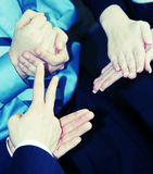 Hand gestures. Close-up on three businesspeople's hands playing hands, rocks, scissors Stock Images