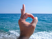 Hand gestures on marine background. Hand silhouette on sea sand background with gestures Stock Photography
