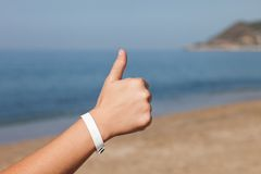 Hand gesturing thumb up on sea beach Stock Photography