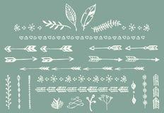 Hand getrokken uitstekende pijlen, veren, verdelers en bloemenelementen Stock Foto's