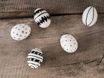 Hand gezeichnete Ostereier auf einem Holztisch Stockfoto