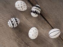 Hand gezeichnete Ostereier auf einem Holztisch Stockfotos