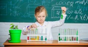 Hand gezeichneter Vektor getrennt auf Weiß Schülerspiel des Mädchens nettes Schulmit Reagenzgläsern und bunten Flüssigkeiten Schu stockbilder