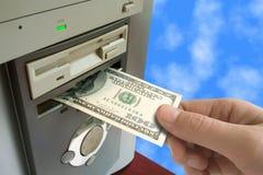 Hand gezet geld aan computer Stock Afbeeldingen