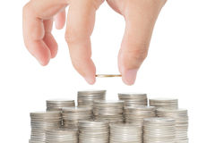 Hand gezet gouden die muntstuk aan stapel muntstukken op witte backgroun worden geïsoleerd Stock Foto