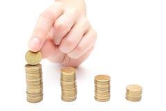 Hand gezette muntstukken aan stapel muntstukken Stock Afbeeldingen