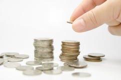 Hand gezette muntstukken aan stapel muntstukken Stock Fotografie