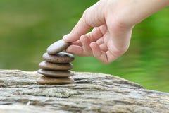 Hand gezette steen die een stapel van zenstenen bouwen Stock Foto