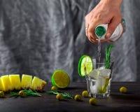 Hand gießt Alkohol in ein Glas mit Eis Oliven, Kalk und rosem Stockfotos