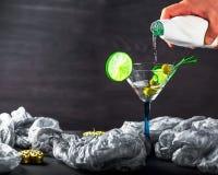Hand gießt Alkohol in ein Glas mit Oliven, Kalk und Rosmarin Stockbilder