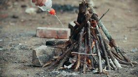 Hand gießt Benzin auf Lagerfeuer und Flamme wird entflammt stock footage