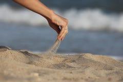 Hand gießt Sand Lizenzfreie Stockfotos