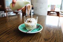 Hand gietende melk in kommen met koekje en roomroomijs Stock Afbeelding