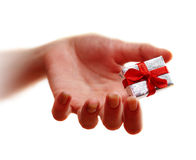 Hand and gift. Emphasis on gift Royalty Free Stock Photo