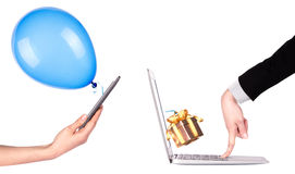 Hand with a gift and laptop Stock Images