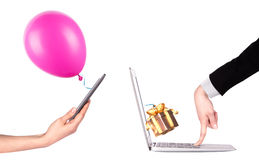 Hand with a gift and laptop Royalty Free Stock Photography