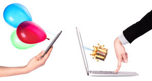 Hand with a gift and laptop Stock Image