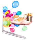 Hand with a gift and laptop. Hand with a gift and balloons come out from a screen of a laptop computer isolated on white background Stock Image