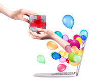 Hand with a gift and laptop Royalty Free Stock Photo