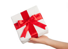 Hand with a gift with a red ribbon isolated Stock Photography