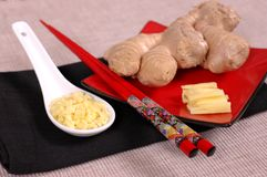 Hand of ginger with minced and sliced ginger. On red plate with chopsticks Royalty Free Stock Photo
