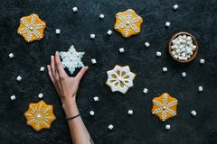 Hand with gingerbread snowflakes and marshmallows. Cropped view of hand with homemade gingerbread snowflakes and marshmallows on black tabletop Stock Photo