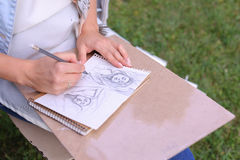 Hand of Girl Artist Makes Sure Sharp Pencil Strokes on Album Pag. Talented Young Woman Handles Details ,obscures Hair in Picture. Sketch Executed Ordinary Pencil Royalty Free Stock Images
