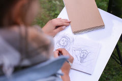 Hand of Girl Artist Makes Sure Sharp Pencil Strokes on Album Pag. Talented Young Woman Handles Details ,obscures Hair in Picture. Sketch Executed Ordinary Pencil Royalty Free Stock Photos
