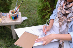 Hand of Girl Artist Makes Sure Sharp Pencil Strokes on Album Pag. Talented Young Woman Handles Details ,obscures Hair in Picture. Sketch Executed Ordinary Pencil Royalty Free Stock Photography