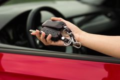 Hand of a girl with a car key in hand, on a red car background royalty free stock photography