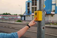 The hand of a girl with a clock presses the button of the pedestrian crossing. The button is lit in red, electronic. Pedestrian crossing. A hand sign indicates stock image
