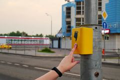 The hand of a girl with a clock presses the button of the pedestrian crossing. The button is lit in red, electronic pedestrian. Crossing. A hand sign indicates stock images