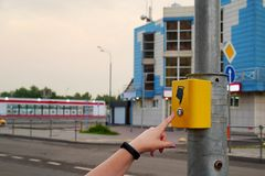 The hand of a girl with a clock presses the button of the pedestrian crossing. Yellow button electronic crosswalk. A hand. Sign indicates a button stock photo