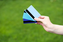Hand girl holding three credit cards. On a background of green grass. Macro Stock Photos