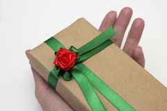 Hand holds a gift for the holiday, Packed in paper and tied with a green ribbon with a red flower rose Stock Images