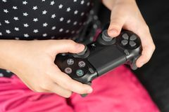 Hand girl playing Sony Dualshock 4. UFA, RUSSIA - NOVEMBER 12, 2017: Hand girl playing Sony Dualshock 4 controller for PlayStation 4 pro. Sony PlayStation 4 pro Royalty Free Stock Photos