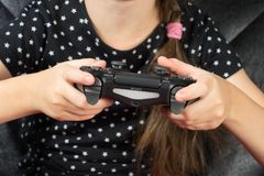Hand girl playing Sony Dualshock 4. UFA, RUSSIA - NOVEMBER 12, 2017: Hand girl playing Sony Dualshock 4 controller for PlayStation 4 pro. Sony PlayStation 4 pro Royalty Free Stock Photo