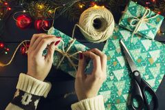 Hand of the girl puts gifts under the Christmas tree. With luminous garlands.Top View. New Year. Christmas background. royalty free stock photos