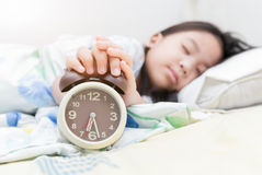 Hand girl reaching out for alarm clock Stock Image
