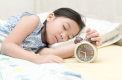 Hand girl reaching out for alarm clock Royalty Free Stock Photo