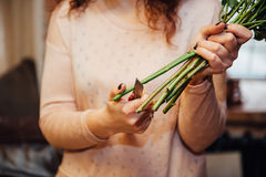 Hand girl with scissors cuts the stalk of flower Royalty Free Stock Photos