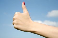Hand girl showing thumbs up. Hand girl showing a thumbs up against the sky Royalty Free Stock Images